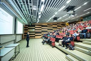 giving presentations man-standing-in-front-of-people-sitting-on-red-chairs-