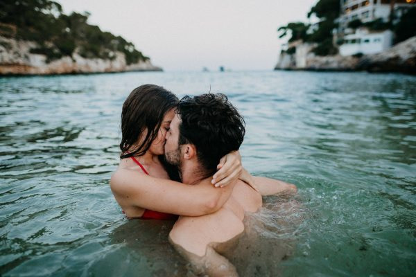 couple swimming and kissing